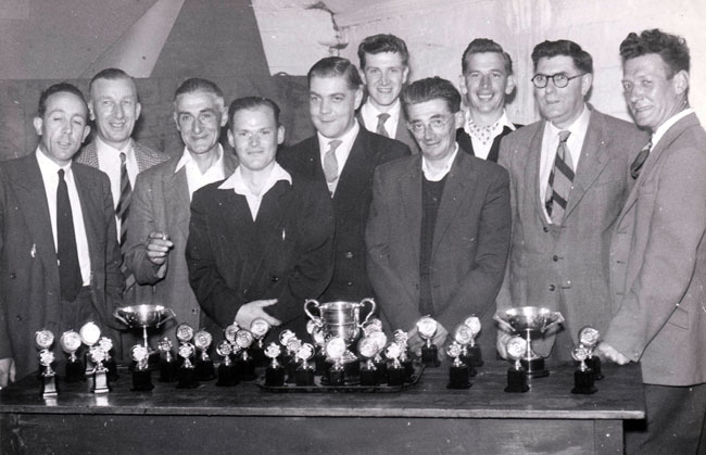 The Royal Oak Skittles Team stand behind a table laden with trophies.