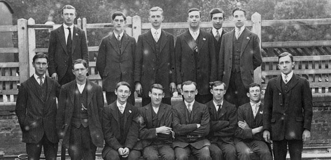 A group of men standing on a railway platform.