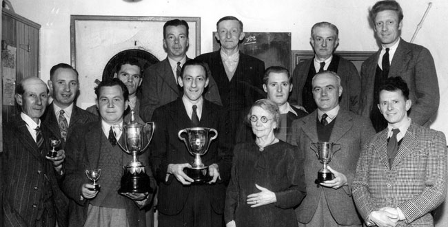 Fanny Brutnell presents trophies to the Kibworth Angling Society in the Royal Oak pub, around 1950.