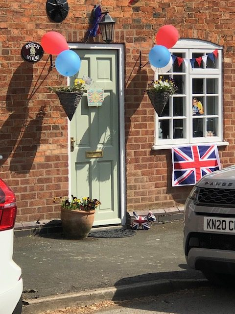Houses decorated with balloons and Union Jack flags.