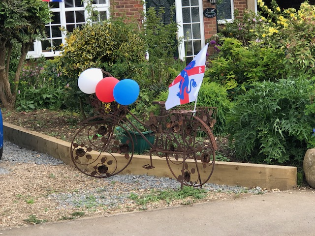 A rusty looking bicycle is decorated with red, white and blue balloons.