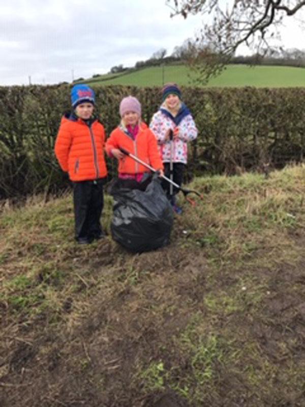 Three brightly dressed children litter picking
